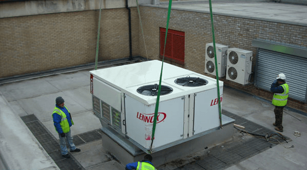 lowering the hvac unit into place for installation